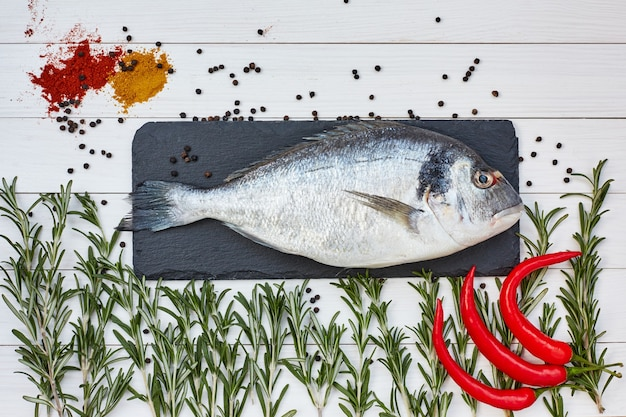 Peixe dourado fresco na tábua de ardósia com alecrim, pimenta fria na mesa branca. vista superior, cópia