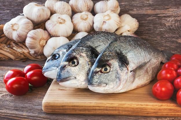 Peixe dourado fresco na tábua de madeira com vegetais em tons