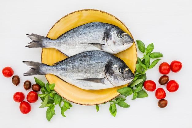 Peixe dourado fresco no prato com legumes. vista do topo