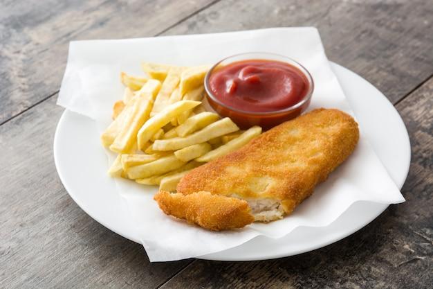 Peixe e batatas fritas britânicos tradicionais na mesa de madeira
