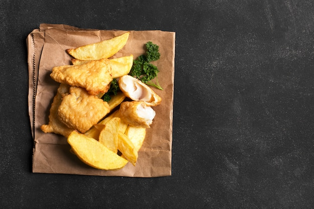 Peixe e batatas fritas britânicos tradicionais na superfície escura