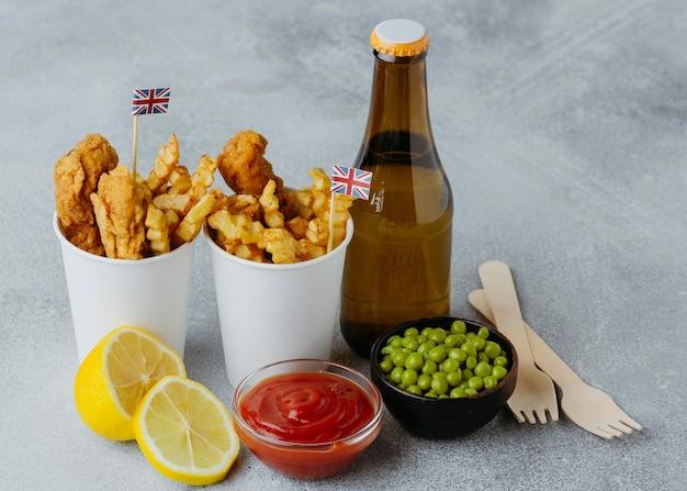 Peixe e batatas fritas em copos de papel com bandeiras da grã-bretanha e garrafa de cerveja em ângulo alto