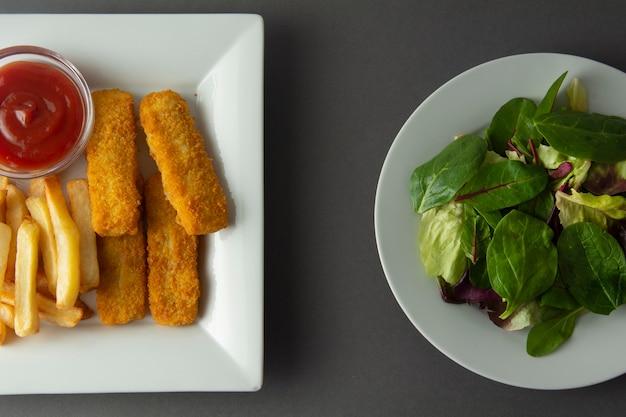 Peixe e chip com salada verde. comida saudável e insalubre.