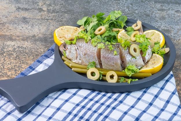 Peixe e legumes numa frigideira de madeira, numa toalha.