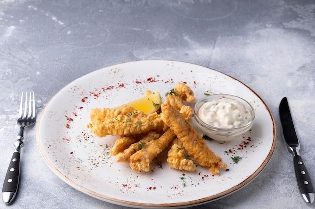 Peixe em massa e molho tártaro servido garfo e faca pronto para comer
