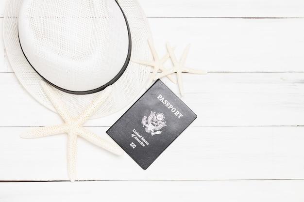 Peixe estrela, passaporte e chapéu em fundo branco de madeira