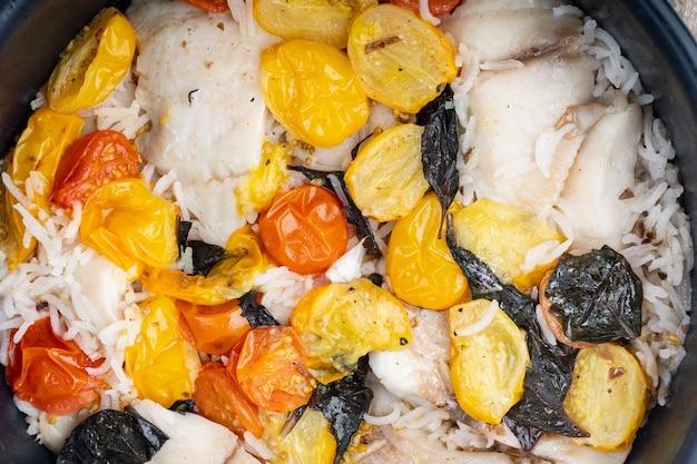 Peixe fabuloso de uma frigideira, com arroz basmati e tomate cereja, vista de cima
