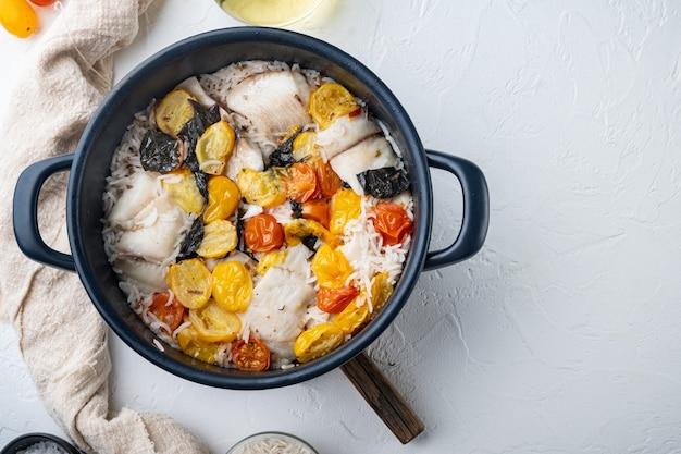 Peixe fabuloso de uma panela, com arroz basmati e tomate cereja, na mesa branca, vista de cima
