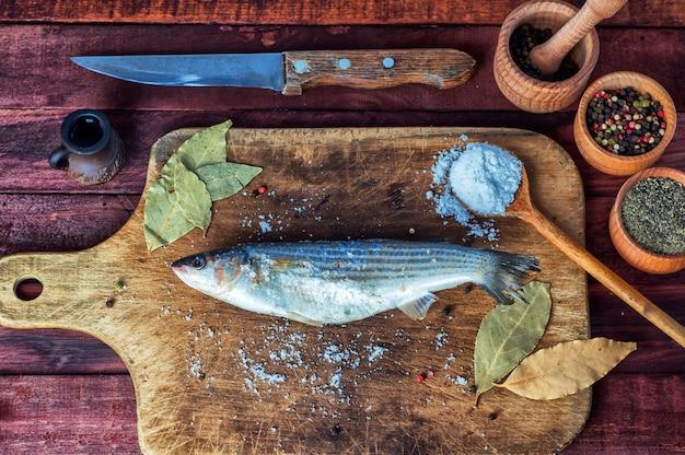 Peixe fresco cheirava para cozinhar em uma placa de cozinha