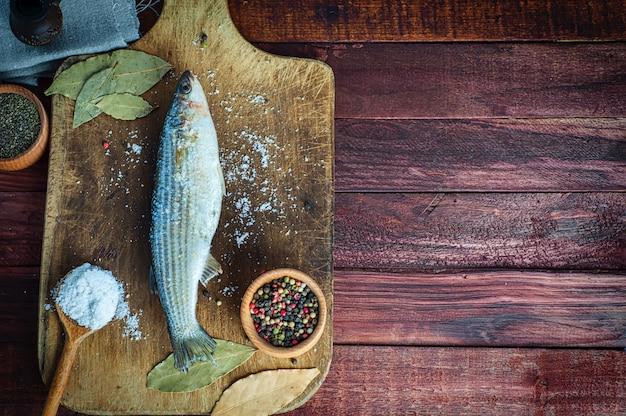 Peixe fresco cheirou a especiarias para cozinhar em uma placa de cozinha