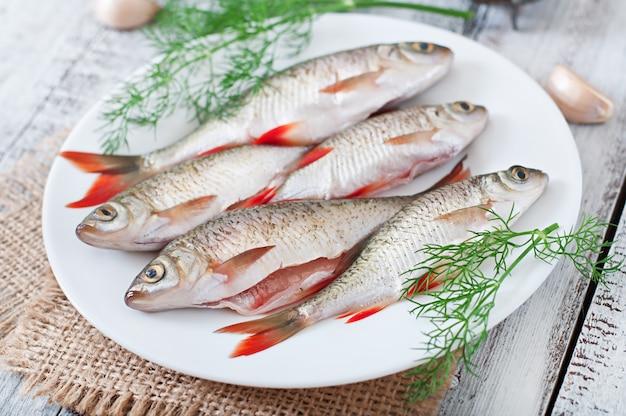 Peixe fresco com alecrim em um prato na mesa de madeira