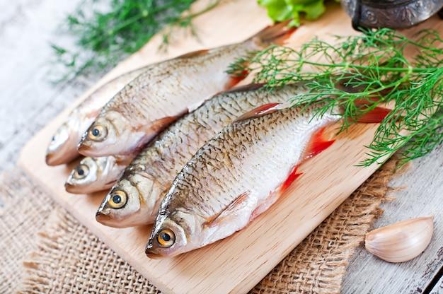 Peixe fresco com alecrim na placa de madeira