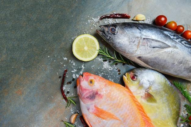 Peixe fresco com ervas especiarias alecrim e limão alho tomate para alimentos cozidos. tilápia de peixe cru vermelho atum e pomfret peixe no escuro