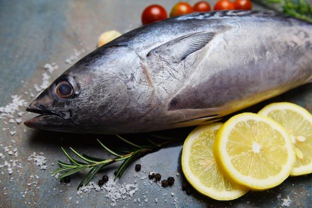 Peixe fresco com ervas especiarias alecrim tomate e limão - frutos do mar peixe cru no fundo da chapa preta, atum longtail, atum pequeno oriental