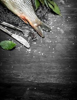 Peixe fresco com ramos de laurel na rede de pesca. sobre um fundo preto de madeira.