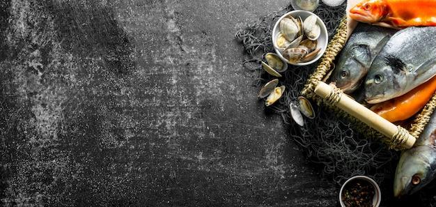 Peixe fresco cru com ostras e especiarias. na mesa rústica escura