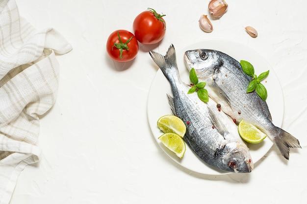 Peixe fresco cru dorado com especiarias e ervas em fundo branco.