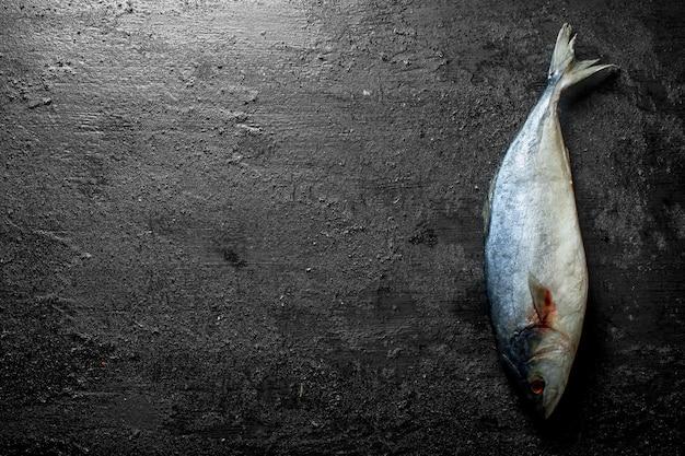 Peixe fresco cru em mesa rústica preta