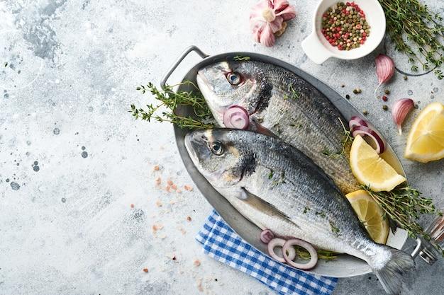 Peixe fresco dourado cru ou pargo com ingredientes para fazer limão, tomilho, alho, tomate cereja e sal sobre fundo de ardósia cinza claro, pedra ou concreto. vista superior com espaço de cópia.