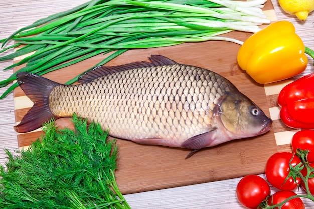 Peixe fresco em uma placa de cozinha com legumes.