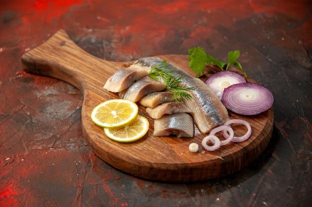 Peixe fresco fatiado de frente com anéis de cebola e limão na refeição escura carne e frutos do mar lanche foto colorida