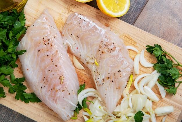 Peixe fresco, filetes de bacalhau cru com adição de ervas e limão