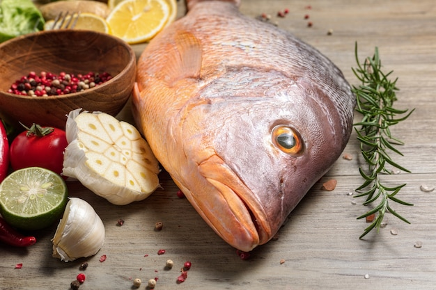 Peixe fresco pargo cru com especiarias, ervas e legumes para cozinhar