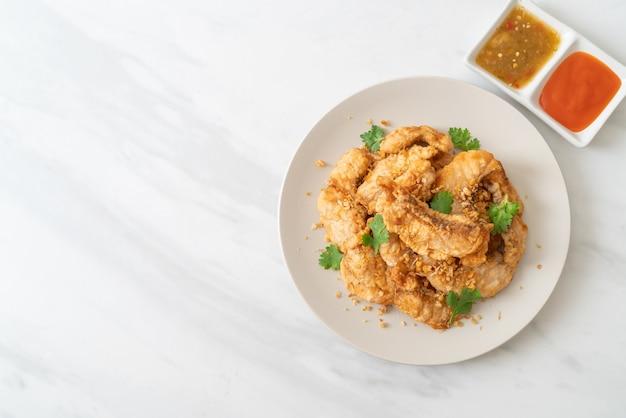 Peixe frito com alho no prato