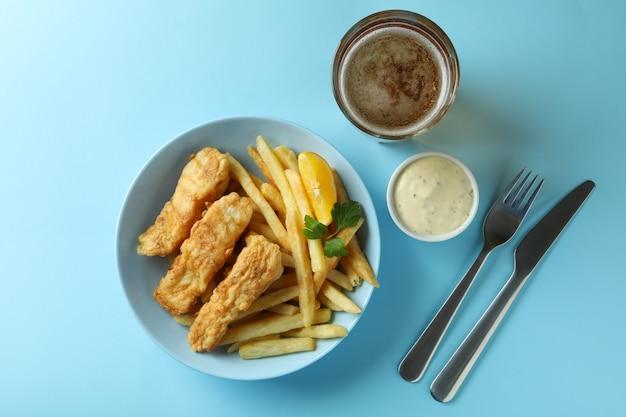 Peixe frito com batata frita e cerveja isolada no azul