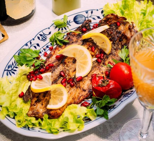 Peixe frito com fatias de romã e limão