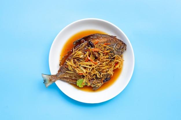 Peixe frito com gengibre e molho de soja no prato de prato branco na superfície azul