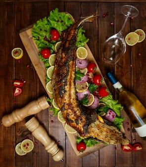 Peixe frito com legumes na placa de madeira