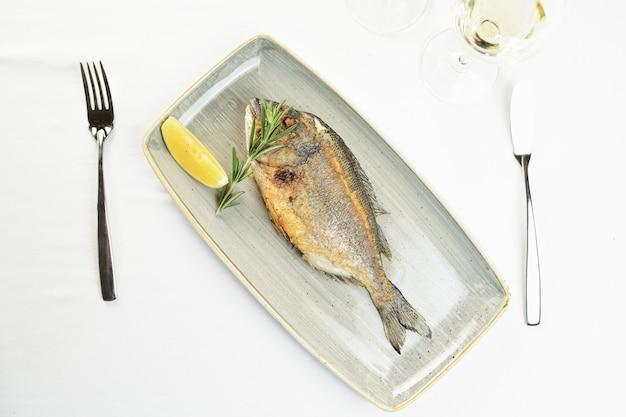 Peixe frito com limão e alecrim em um prato