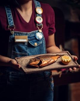 Peixe frito com limão fresco na placa de madeira