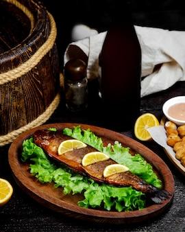 Peixe frito com rodelas de limão em cima da mesa
