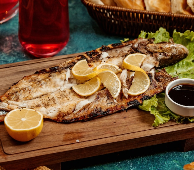 Peixe frito com rodelas de limão em uma placa de madeira