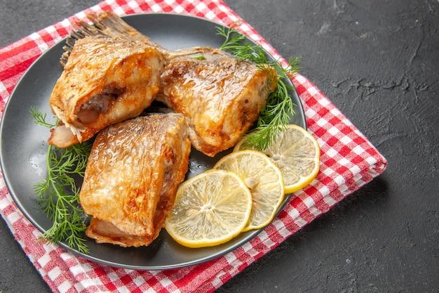 Peixe frito com rodelas de limão no prato e guardanapo em fundo preto.