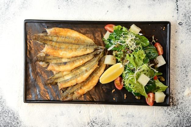 Peixe frito com salada e limão