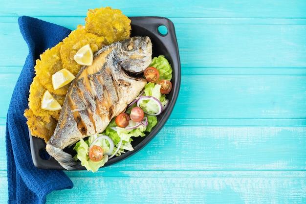 Peixe frito com salada e patacones numa superfície azul. copie o espaço.