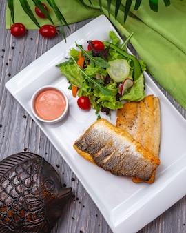 Peixe frito com salada verde alface tomate rúcula rabanete vista superior