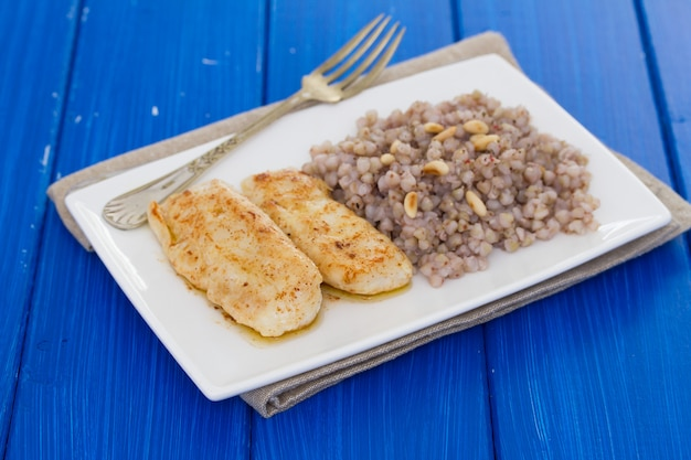 Peixe frito com trigo cozido no prato branco na superfície de madeira