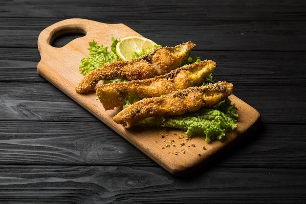 Peixe frito crocante em uma placa de madeira rústica