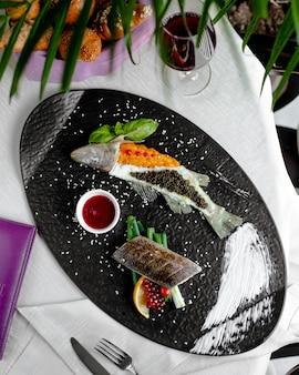 Peixe frito decorado com caviar vermelho e preto e servido com molho