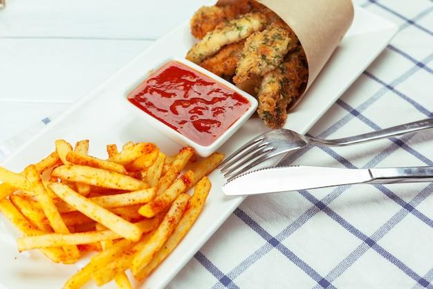 Peixe frito e batatas fritas no prato branco