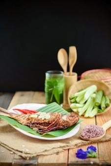 Peixe frito em conserva com acompanhamentos na mesa de madeira e fundo preto