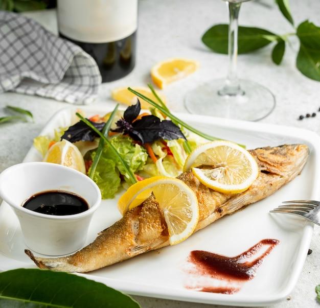 Peixe frito, guarnecido com rodelas de limão, servido com salada e nar sharab