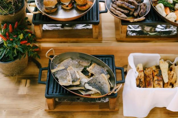 Peixe frito na frigideira da cozinha com pão focaccia e pratos quentes para banquete