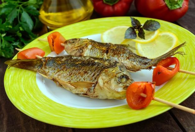 Peixe frito no espeto com pimenta e limão