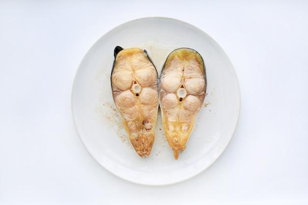 Peixe-gato listrado cortado cozinhado na placa branca contra o fundo branco.
