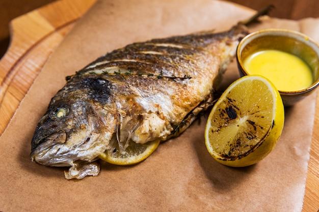 Peixe grande com limão e molho na mesa de madeira no restaurante de luxo